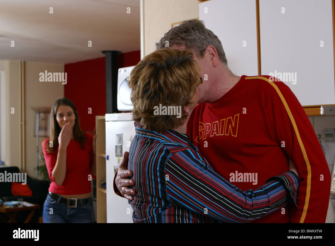 Teenage girl catches mom and dad kissing in the kitchen and laughs at it. SerieCVS217053 - Stock Image