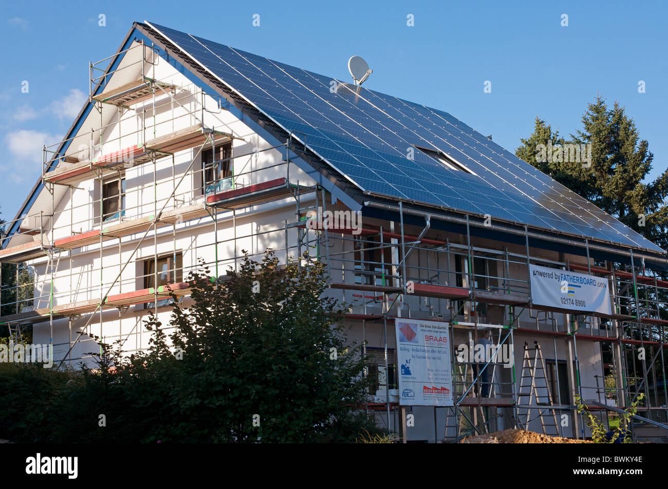 House under construction with solar energy panels covering the whole rooftop - Stock Image