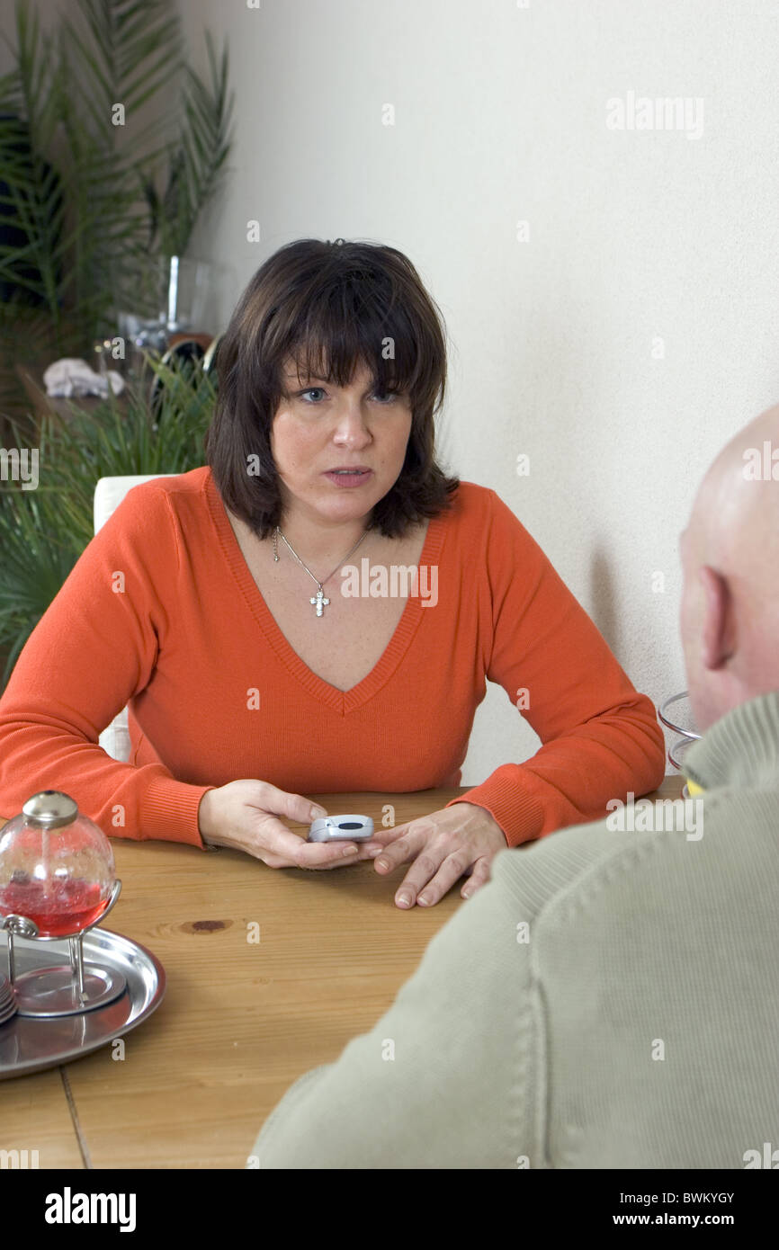 woman finds out cheating by checking husbands cellphone - Stock Image