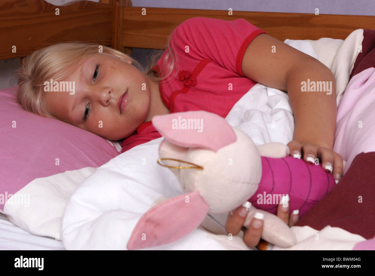 Sick child in bed with cuddle - Stock Image