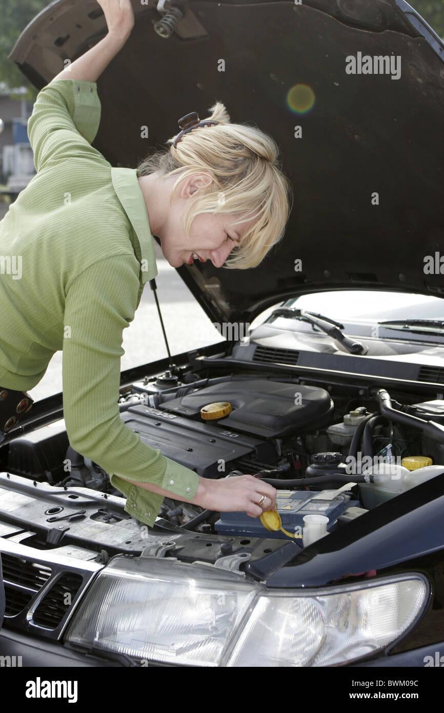 Woman fixing car looking woman under hood of car - Stock Image