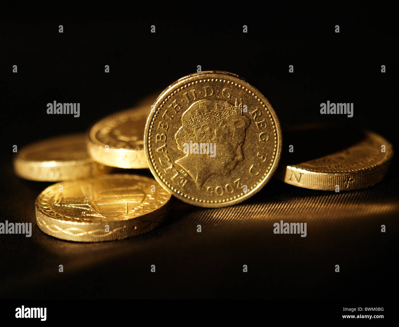 British pound coin with soft lighting stood up amongst other pound coins - Stock Image