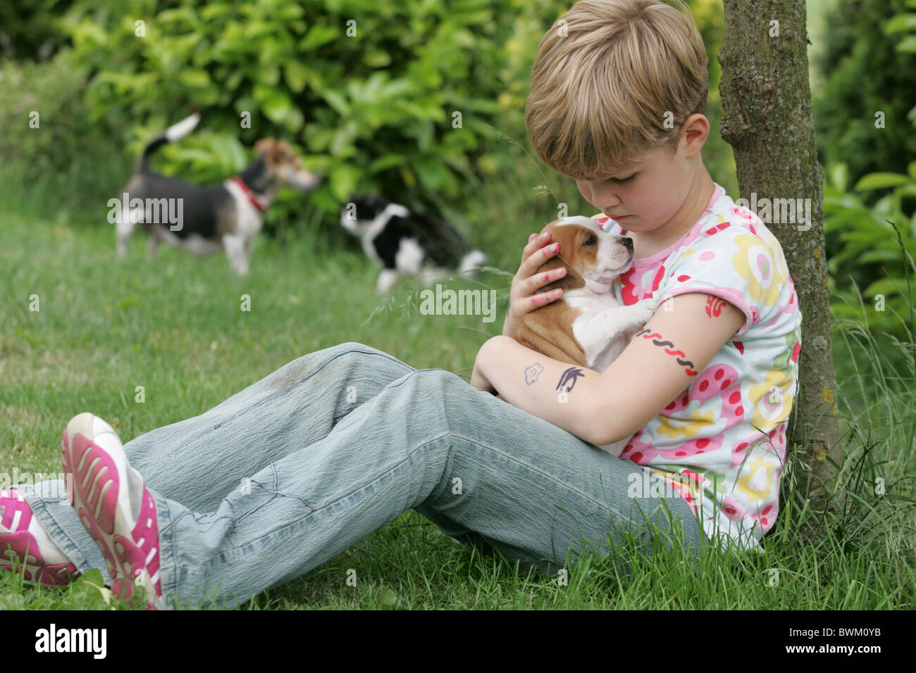Lonely Boyish Girl Cuddling Her Puppy Dog And Mother Dog Protecting