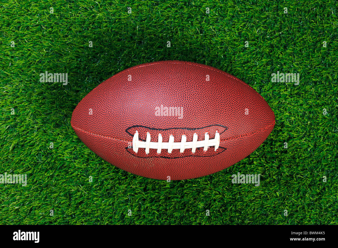 An American football on grass - Stock Image