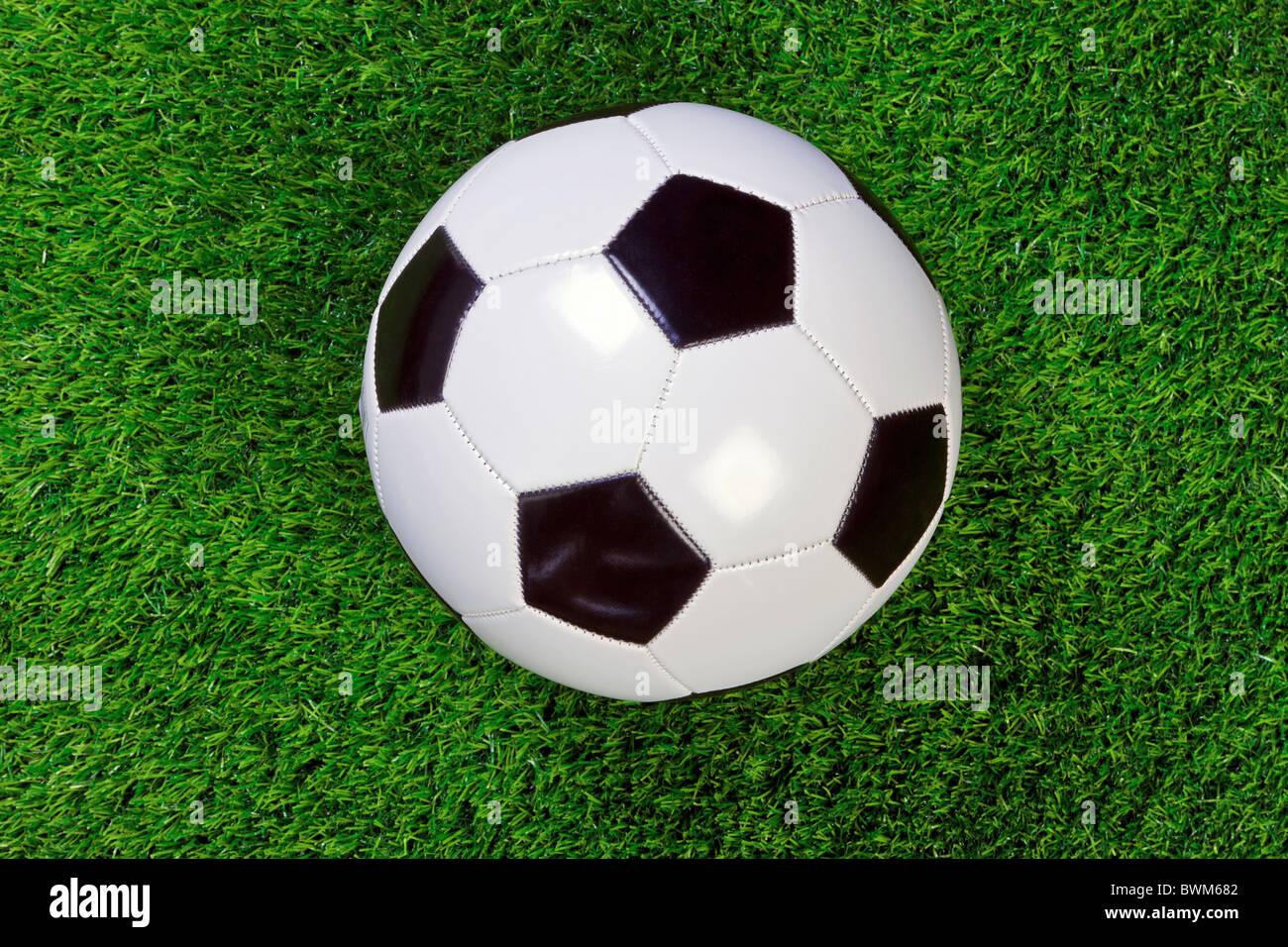 A white and black chequered leather football or soccer ball on grass. - Stock Image