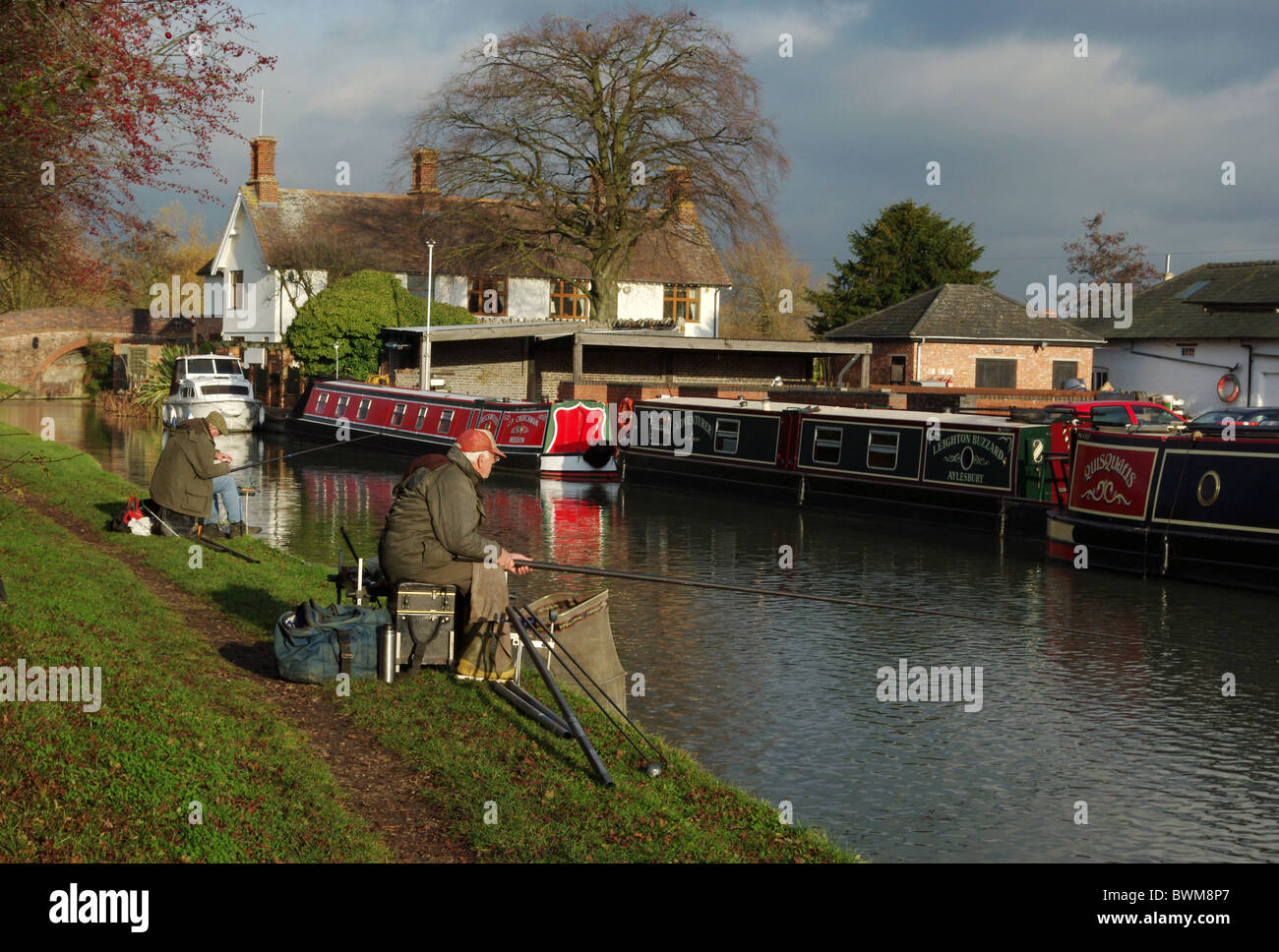 Two fishermen on the banks of the Grand Union Canal at Blisworth Arm, Northamptonshire, UK - Stock Image