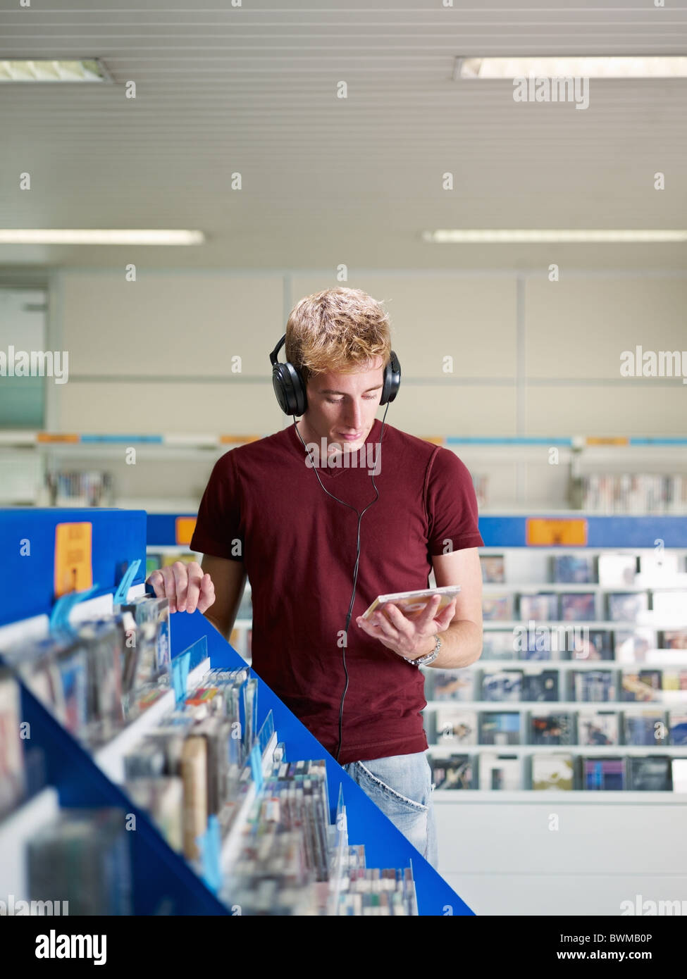 caucasian man with headphones, choosing cd in music shop. Vertical shape, front view, waist up, copy space - Stock Image