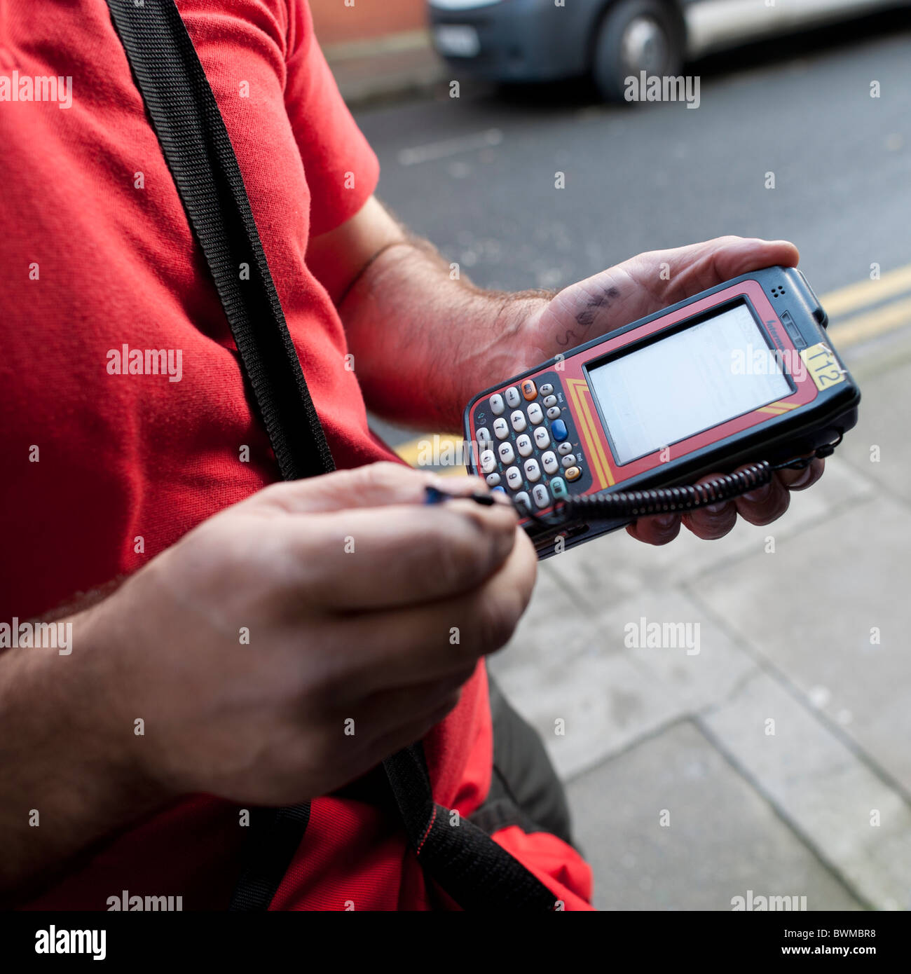 a Royal Mail postman using a hand-held digital device to record delivery of an item of mail, UK - Stock Image