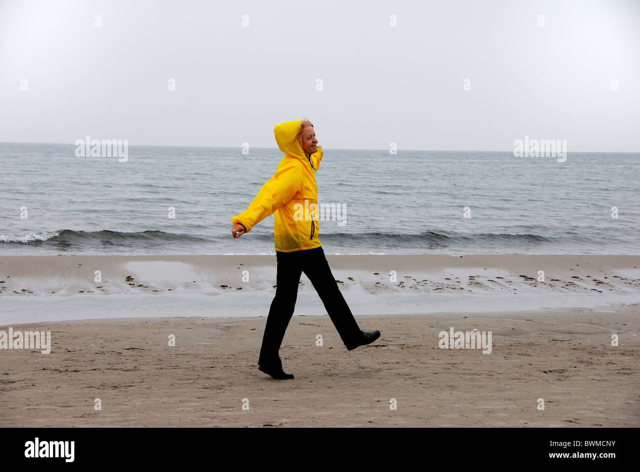Germany Europe Baltic Sea rain storm Windy Breezy Uncomfortable female seniors mature woman rain clothing - Stock Image