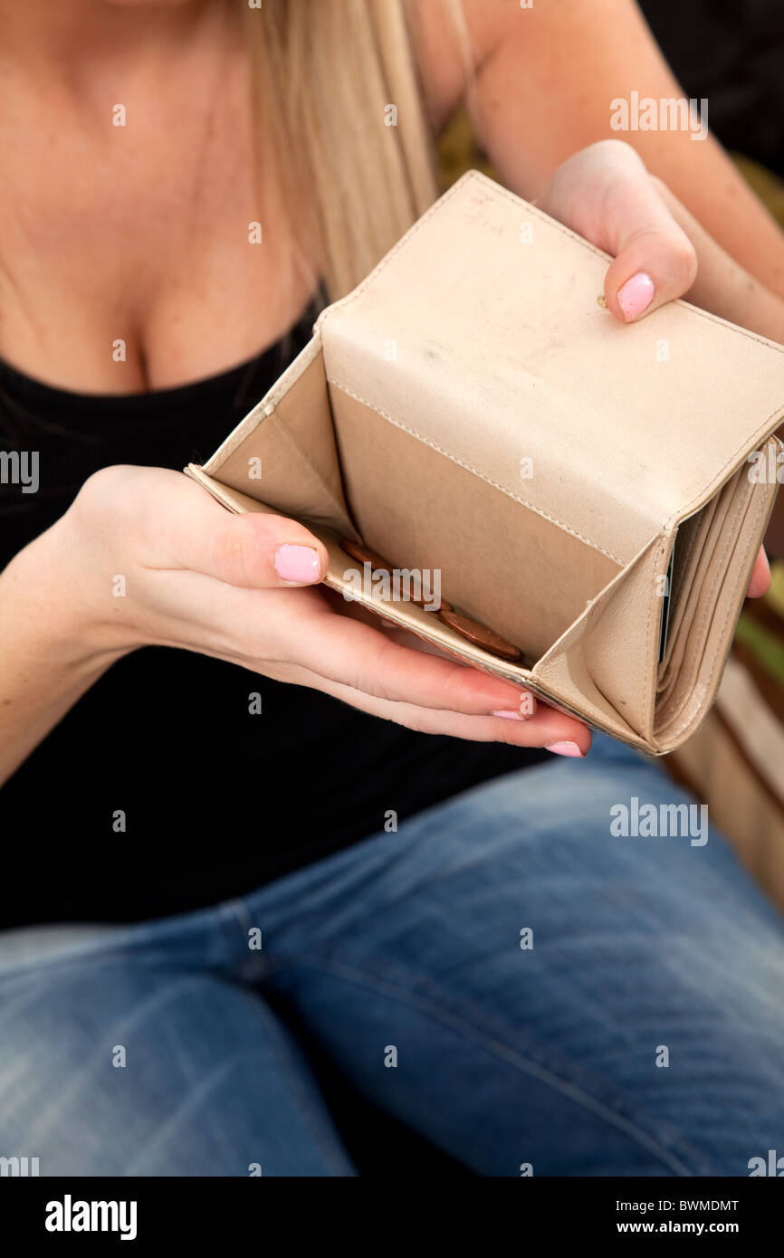 Young woman with only loose change in her purse. - Stock Image