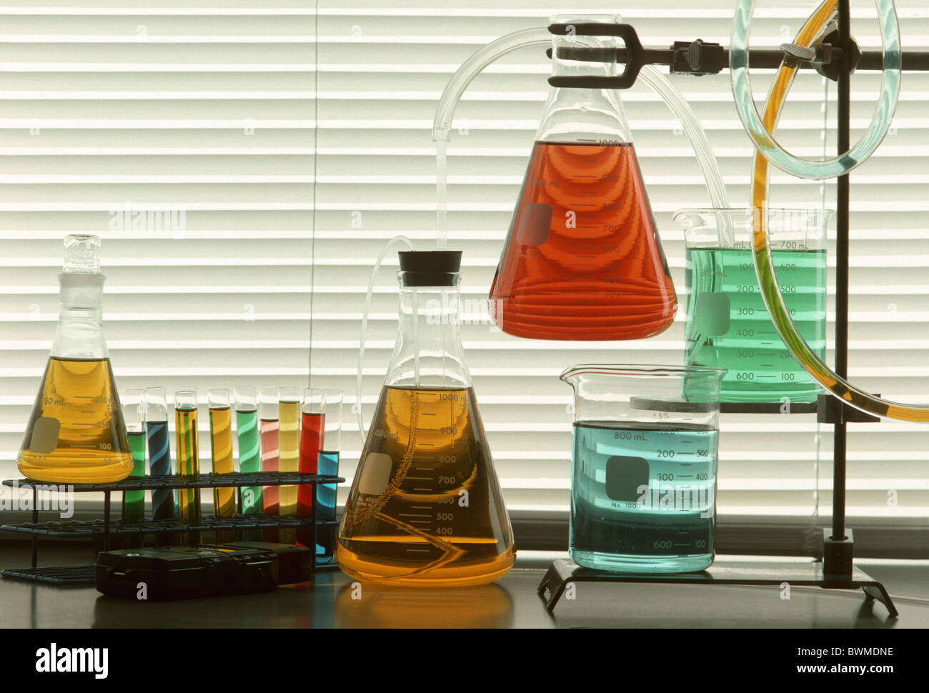 Scientific glassware and tubes filled with colored liquids against window blinds Stock Photo