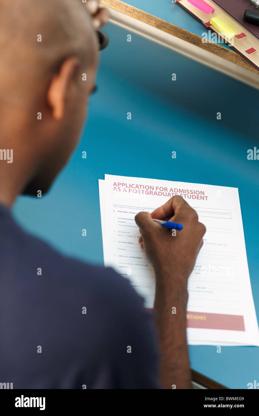 guy filling in application form for postgraduate courses - Stock Image