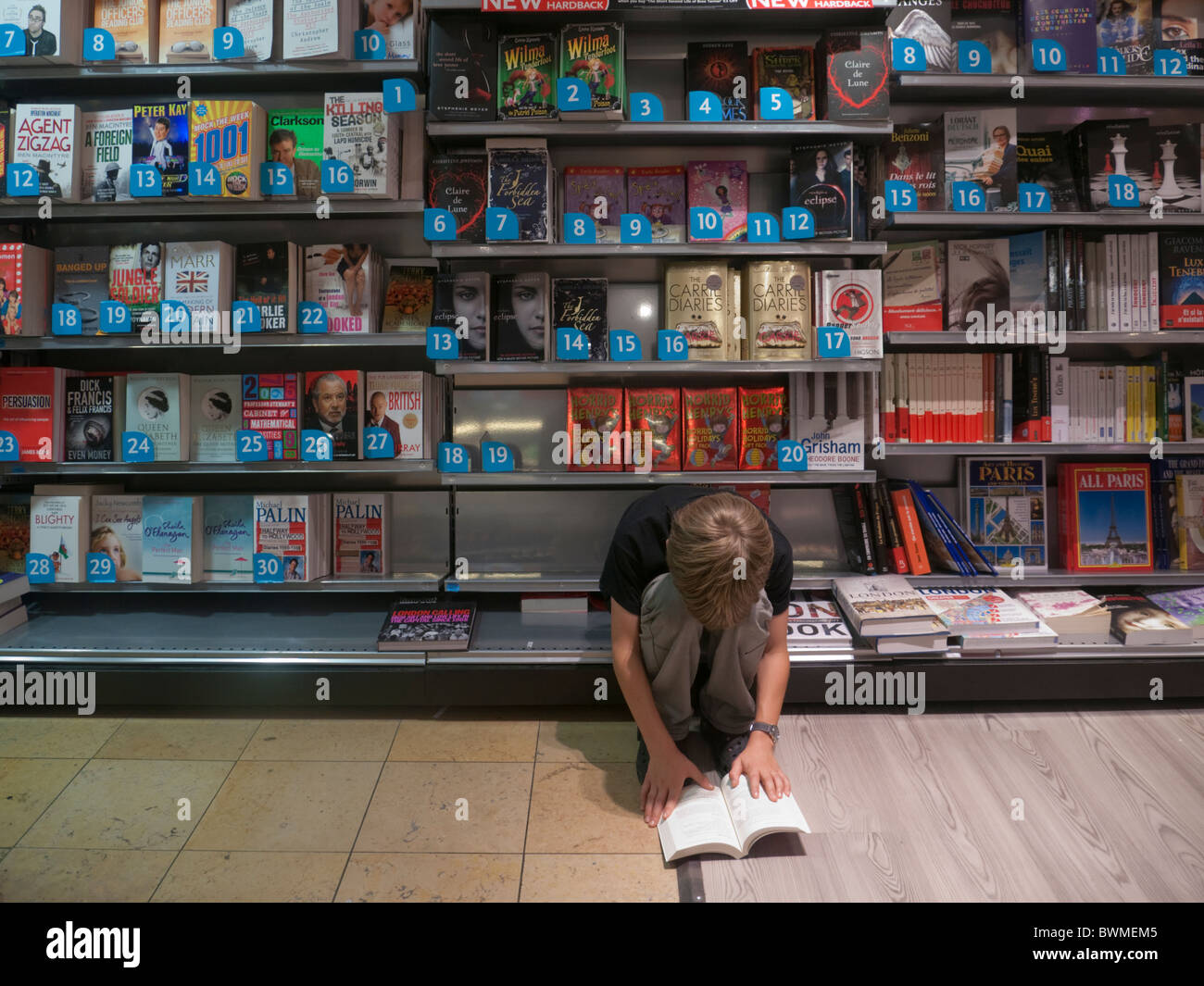 Ten year old boy reads in WH Smith bookshop at Sangatte channel tunnel - Stock Image