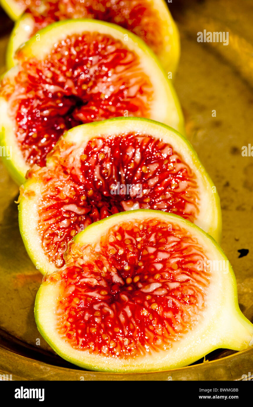 Fresh green figs cut open to show the sweet, sticky and red seeds. On an old brass plate. - Stock Image
