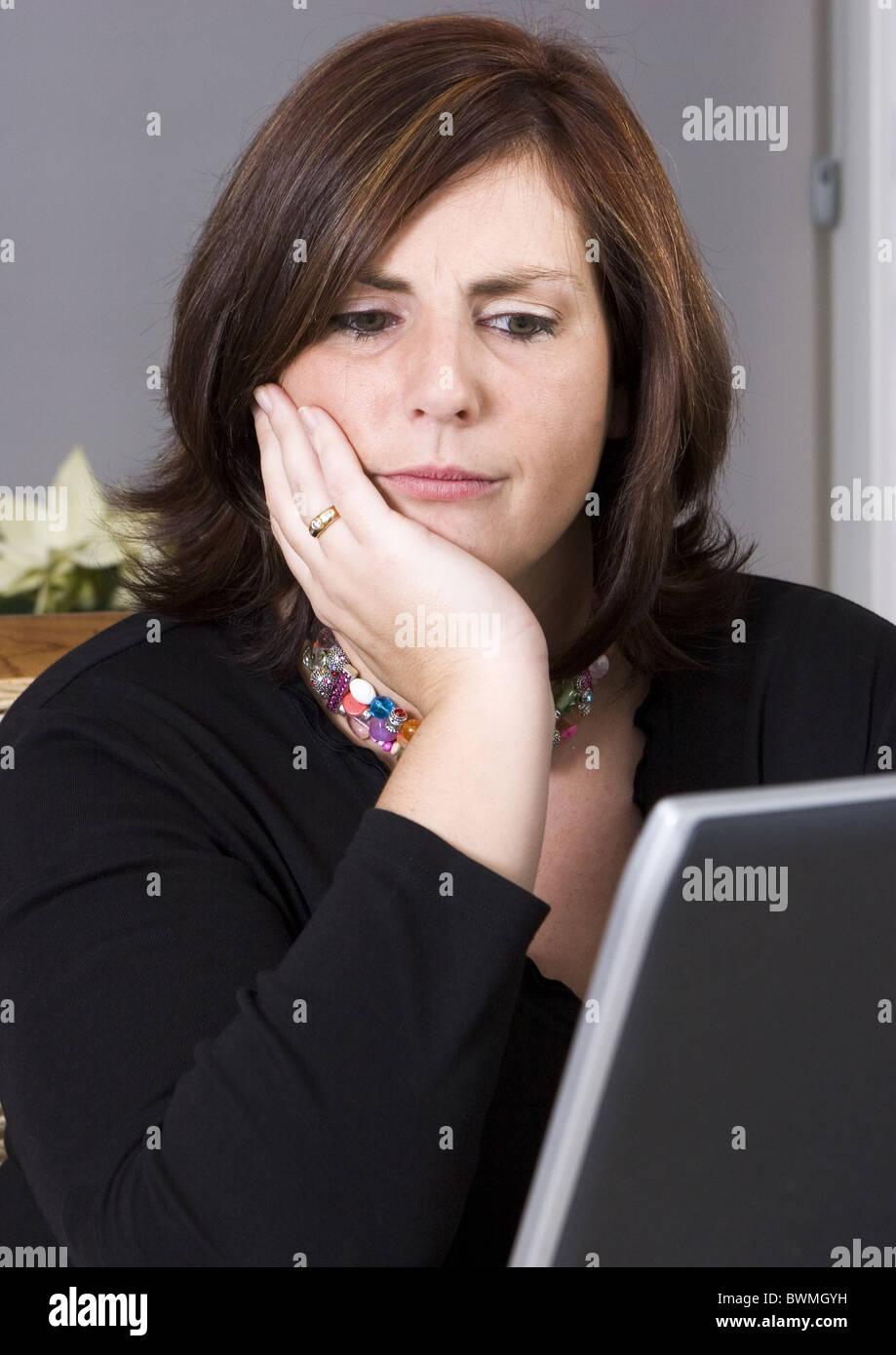 Moody woman behind computer screen - Stock Image