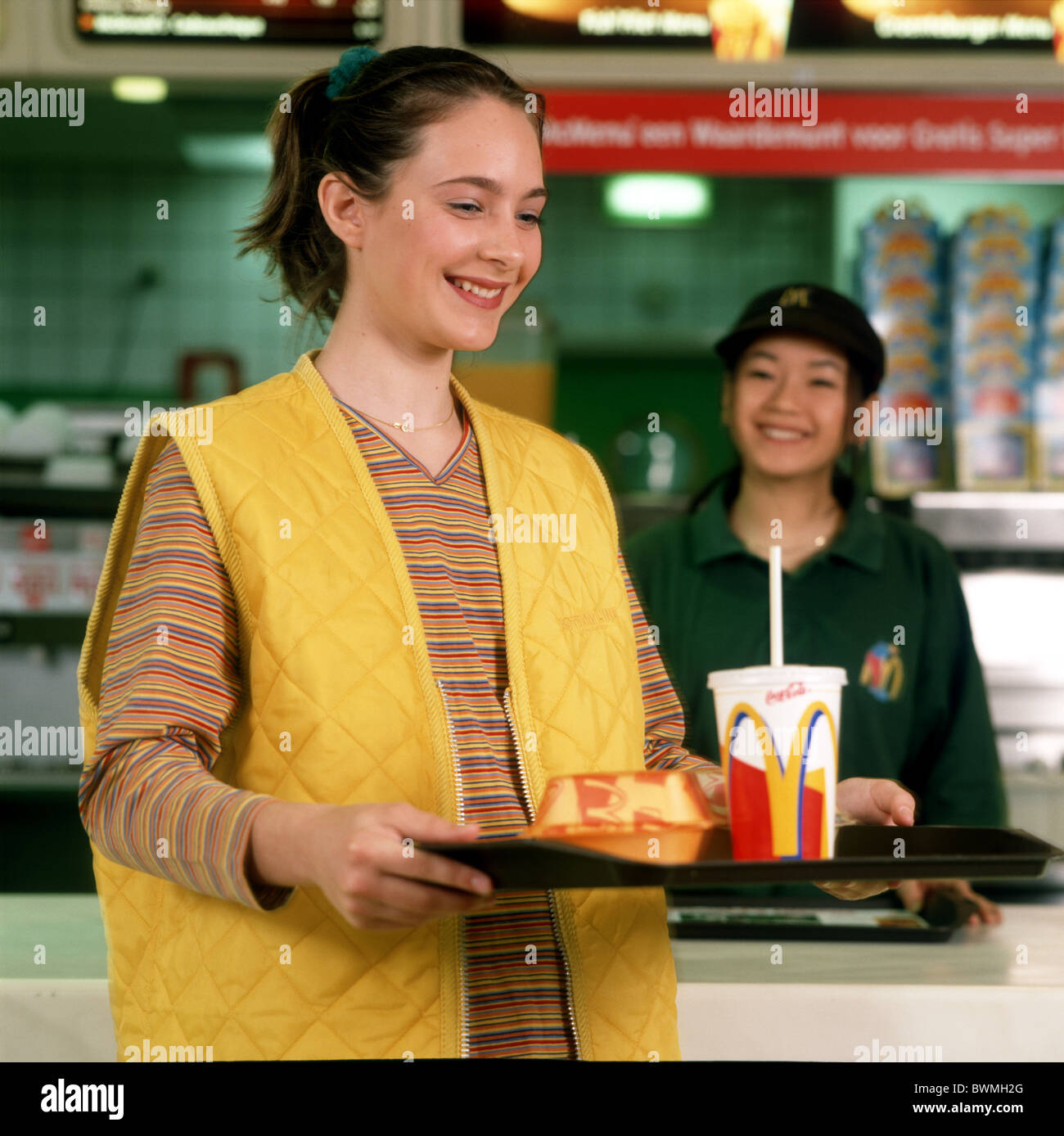 1990s : McDonalds meal in restaurant : Teenage girl carrying plate and friendly female servant in background. - Stock Image