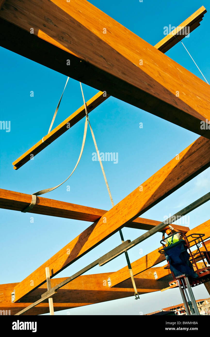 Workman building a structural glulam frame on a cherry picker - Stock Image