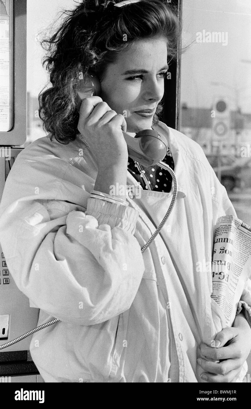 1980s :Young lady standing in telephone boot with phone in hand and newspaper in other hand. - Stock Image