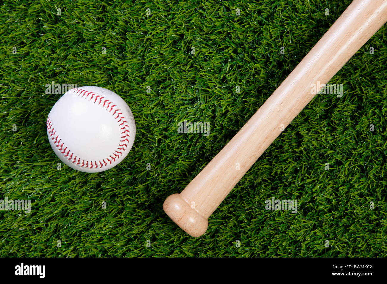 Photo of a baseball and wodden bat on grass - Stock Image