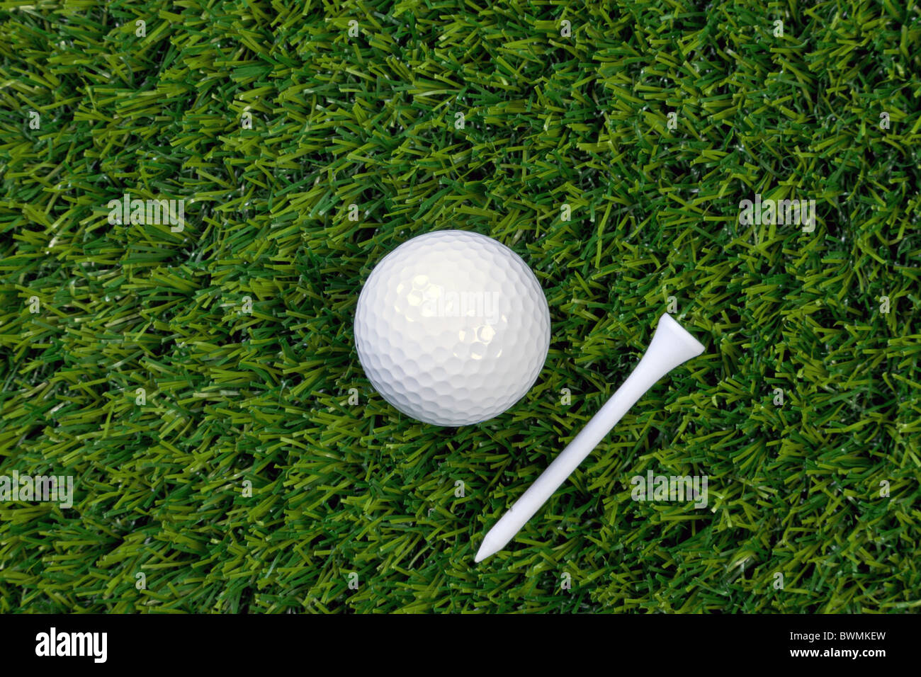 A photo of a golf ball and wooden tee on grass - Stock Image