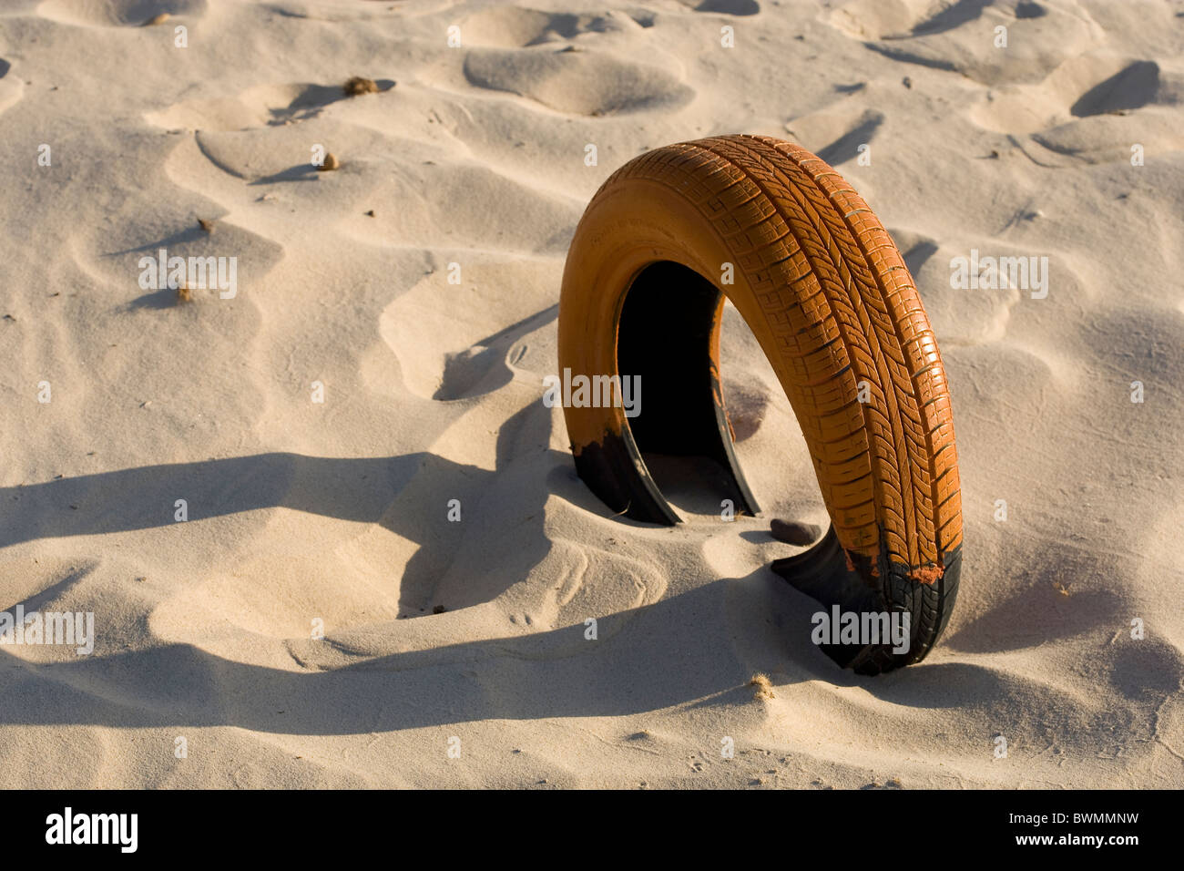 orange painted car tyre sunk into sand  - Stock Image