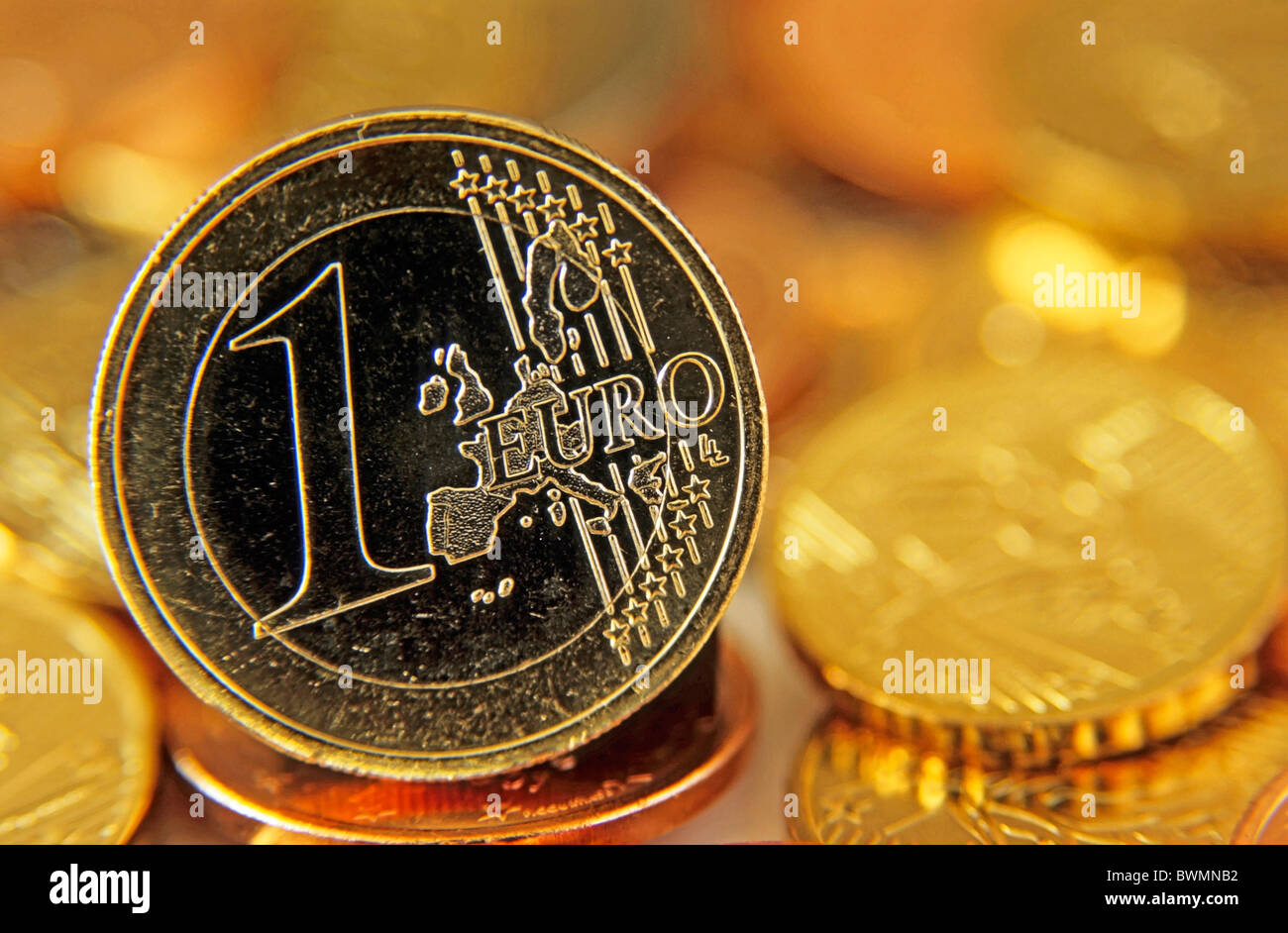 One Euro coin standing up amongst other Euros - Stock Image