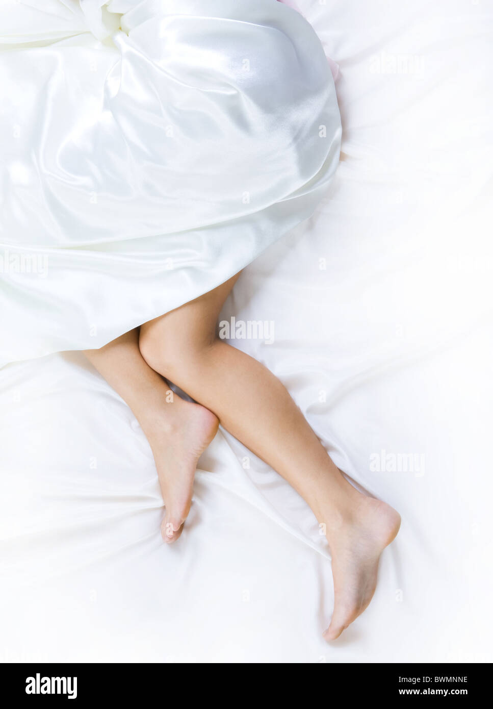 Image of barefooted female legs pointing out of white silk blanket - Stock Image