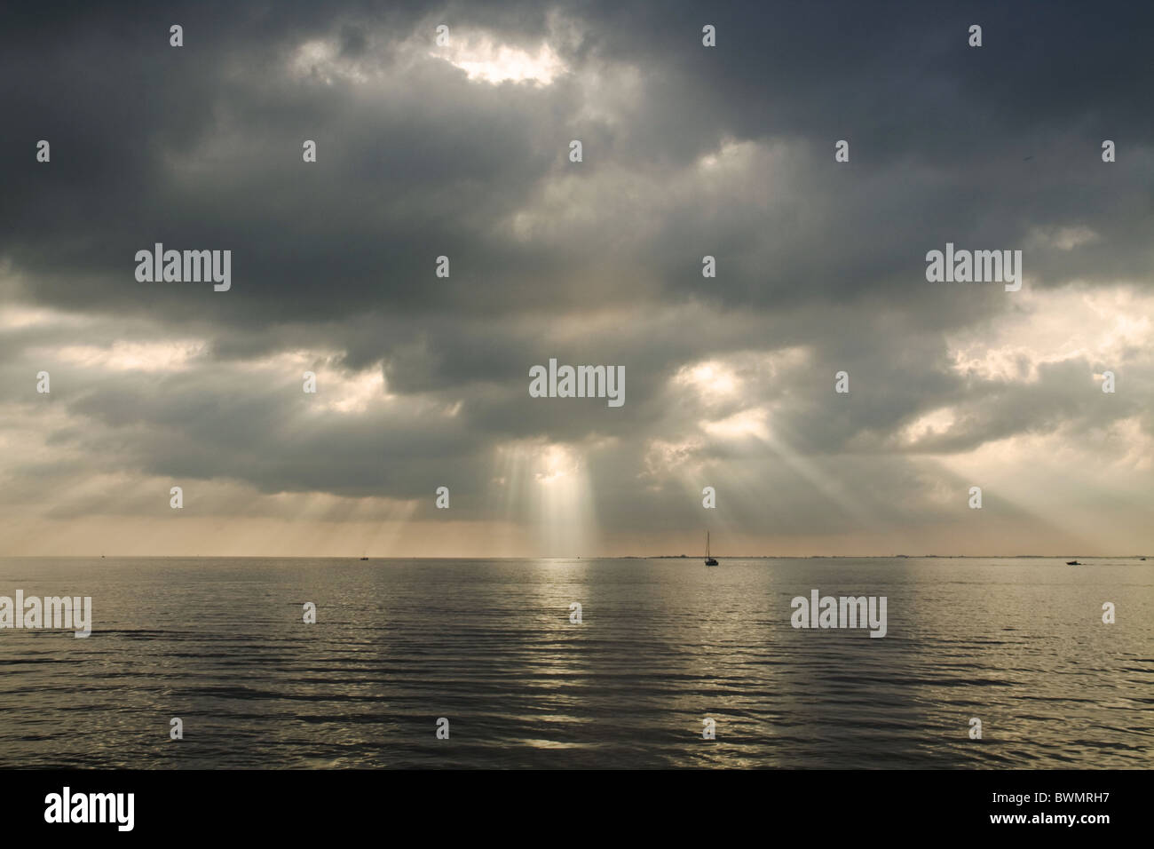 Sun Beams piercing the clouds and reflecting with silver light on the sea in a cold day of November Stock Photo