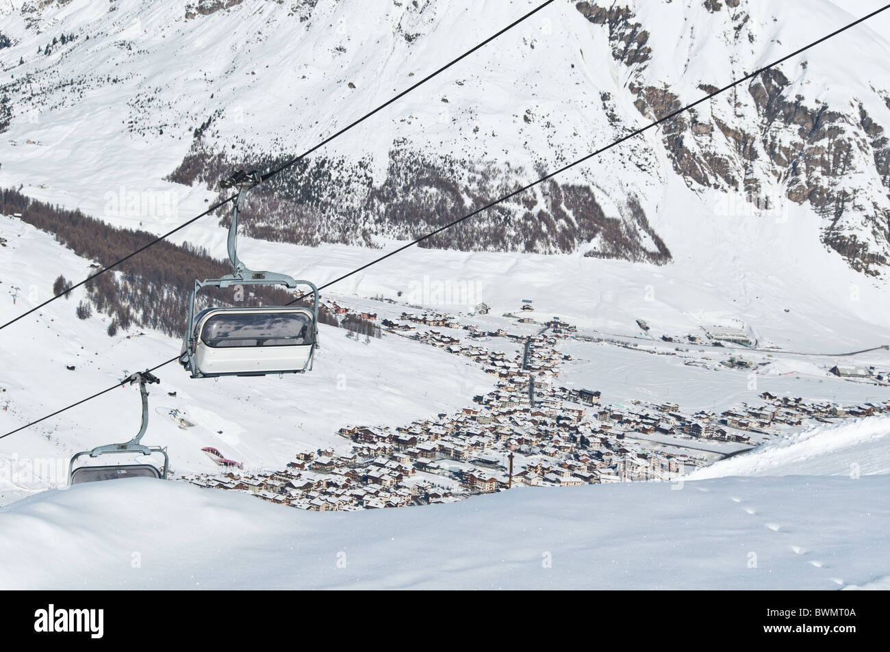 Chairlifts running above a mountain village - shot in Livigno, Italian Alps Stock Photo