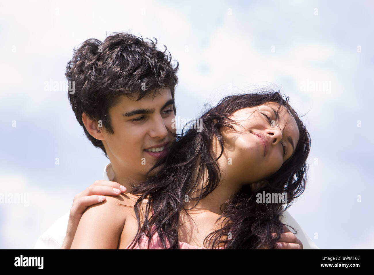 Photo of handsome man embracing tenderly beautiful woman on background of sky - Stock Image