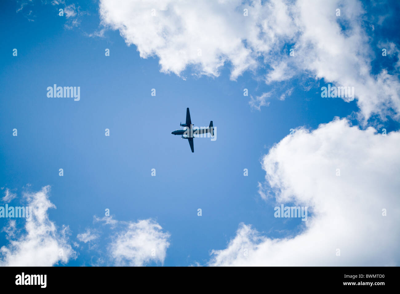 Photo of flying aircraft in bright cloudy sky - Stock Image