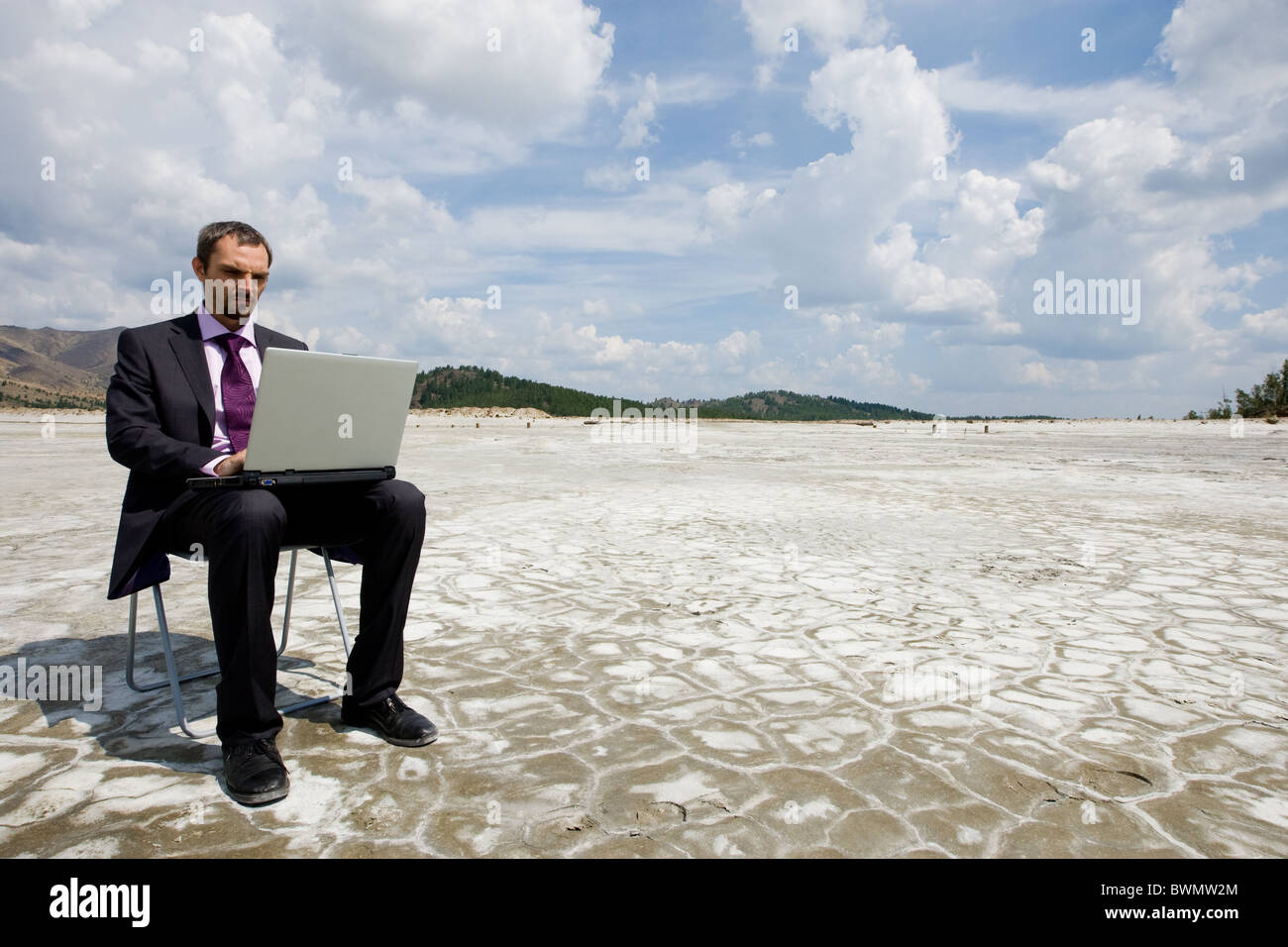 Photo of modern businessman typing on laptop outside with cloudy sky above - Stock Image