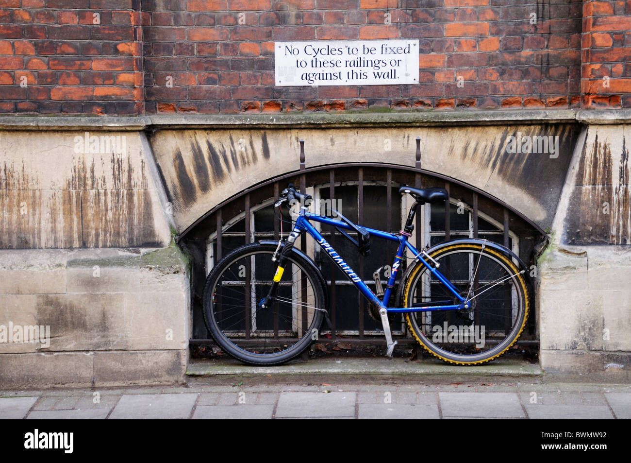 No Cycles to be fixed to these railings or against this wall sign, with chained up bicycle below, Cambridge, England, - Stock Image