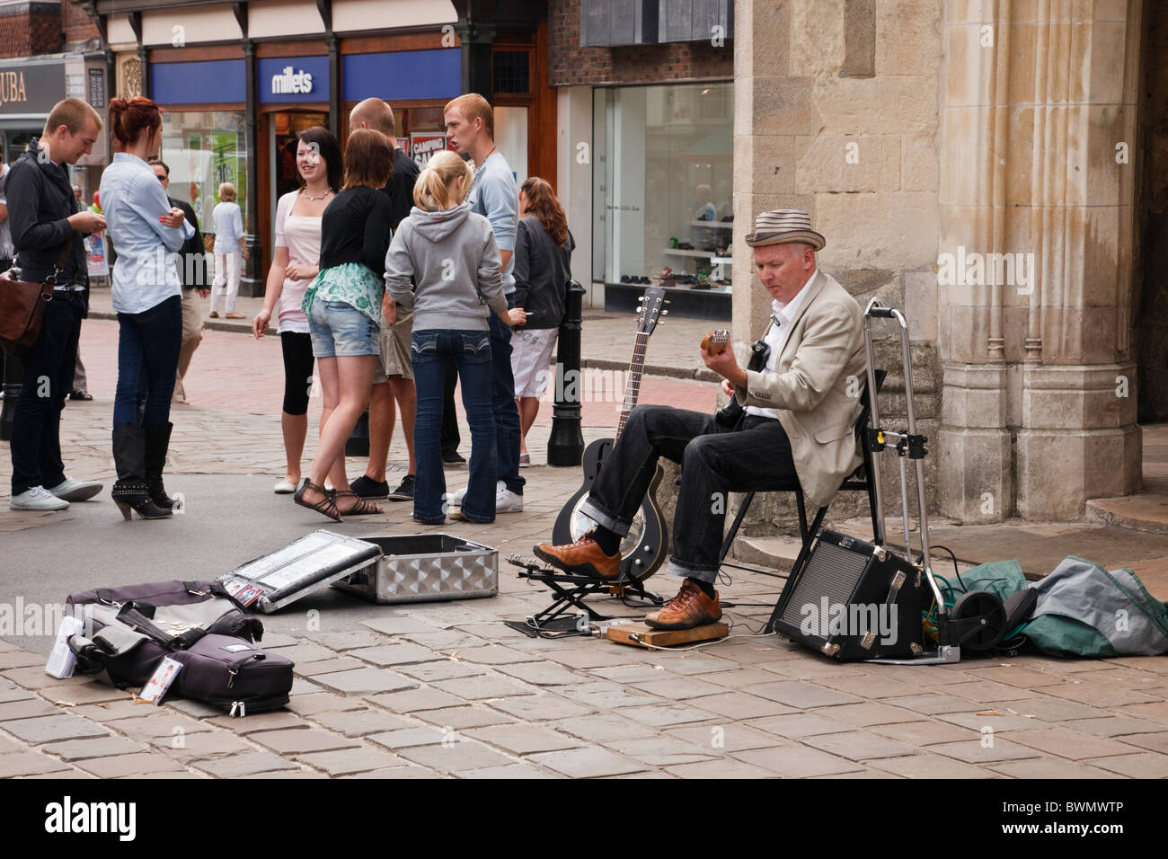 Street busker playing a guitar to collect money by old market cross in city centre in Chichester, West Sussex, England, - Stock Image