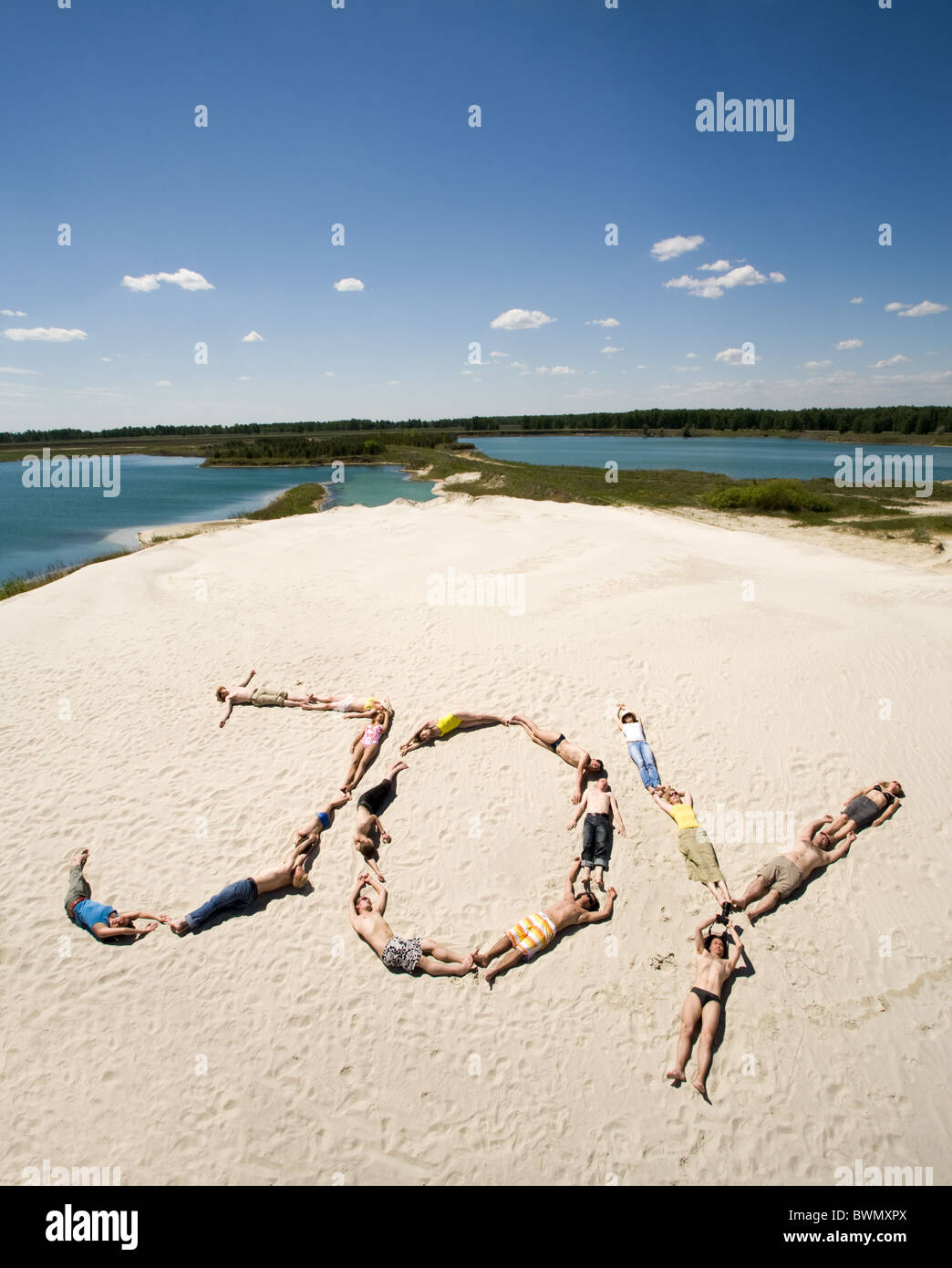 Image of word joy made up of young people sunbathing with sea and sky at background - Stock Image