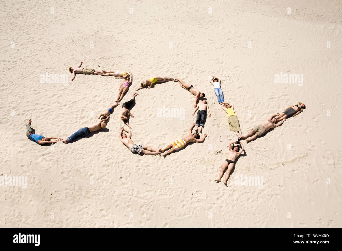Image of word joy made up of young people resting on the sand - Stock Image