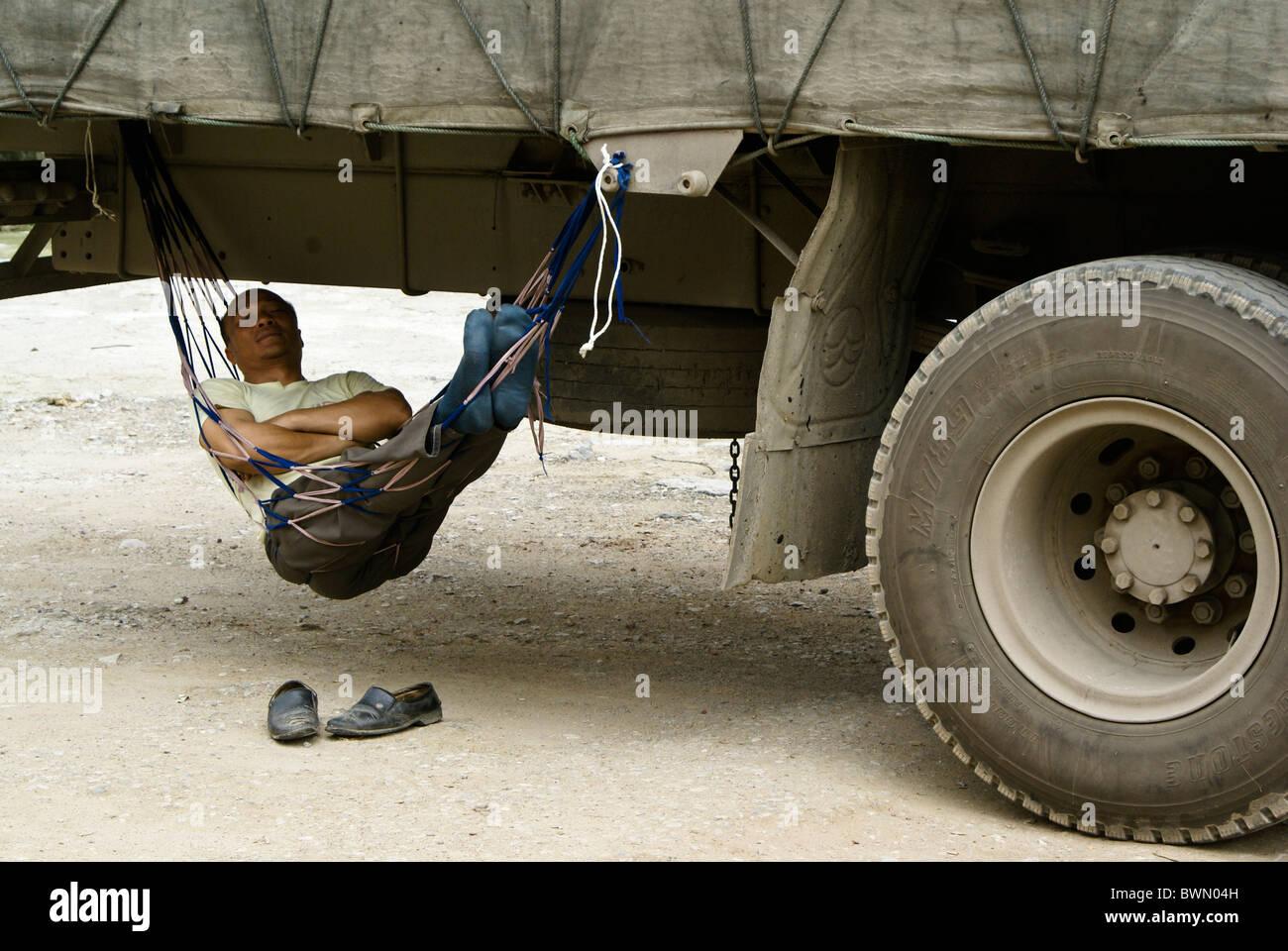 Man sleeping in hammock under his truck, Fuli, Guangxi, China - Stock Image