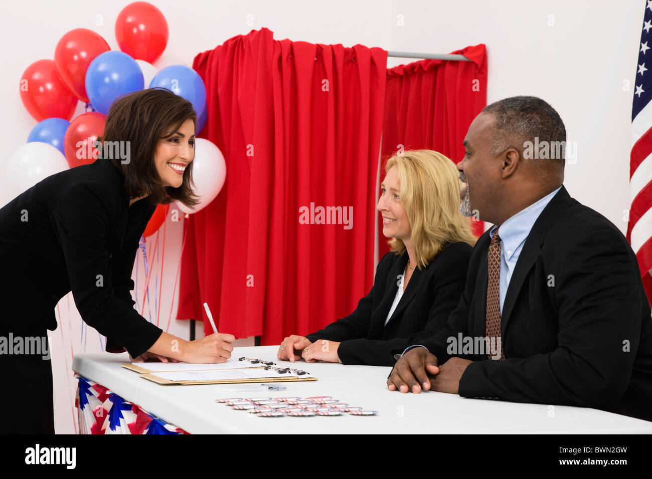 USA, Illinois, Metamora, People at polling place table, US flag, balloons and voting booth in background - Stock Image