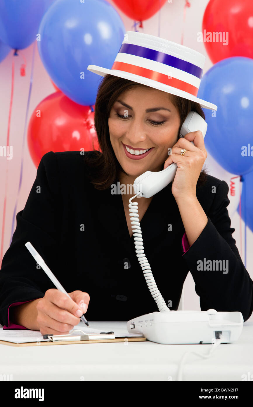 USA, Illinois, Metamora, Smiling woman wearing hat talking on phone, red and blue balloons in background - Stock Image