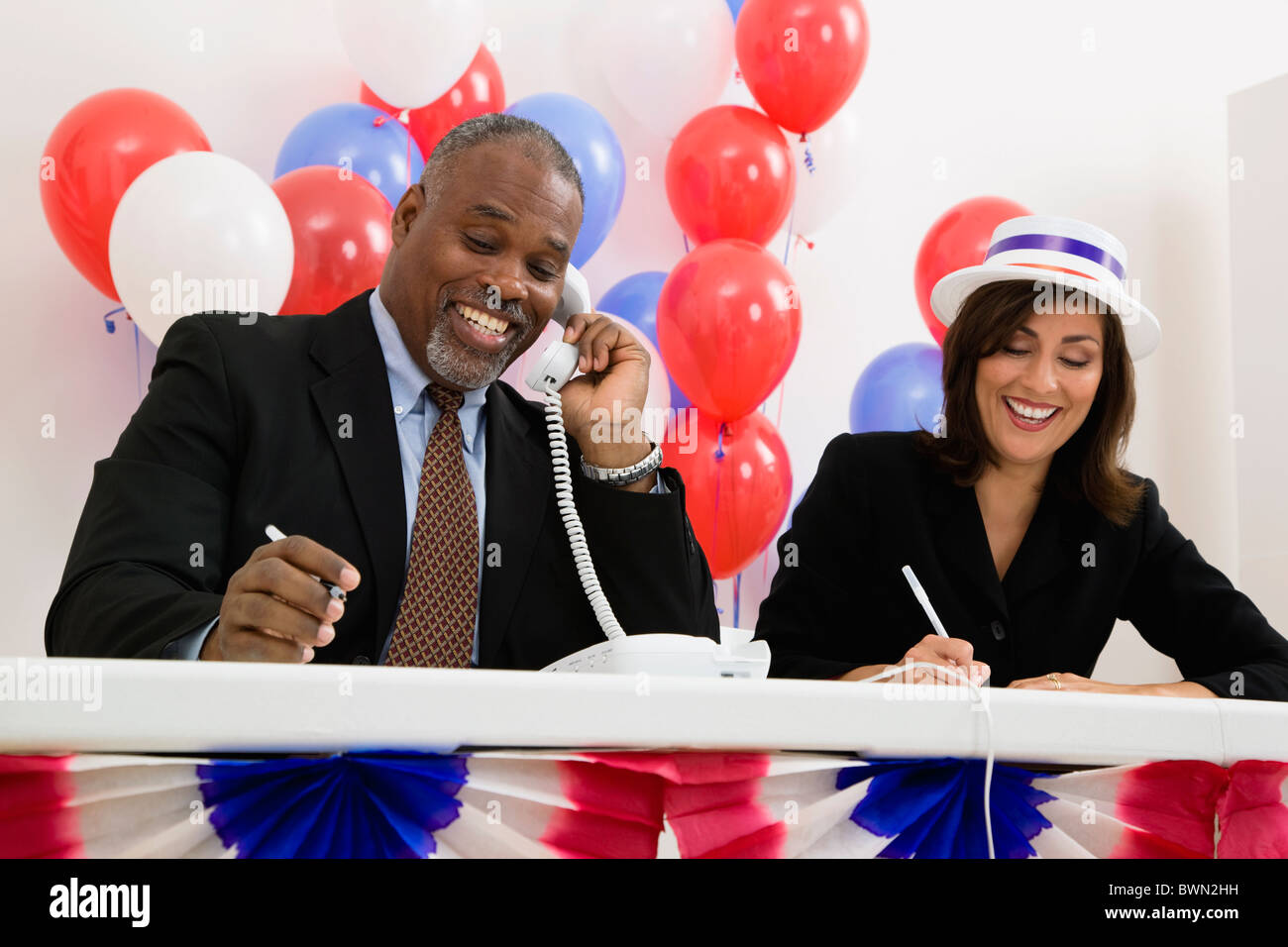 USA, Illinois, Metamora, Smiling man and woman at polling place table, red and blue balloons in background - Stock Image