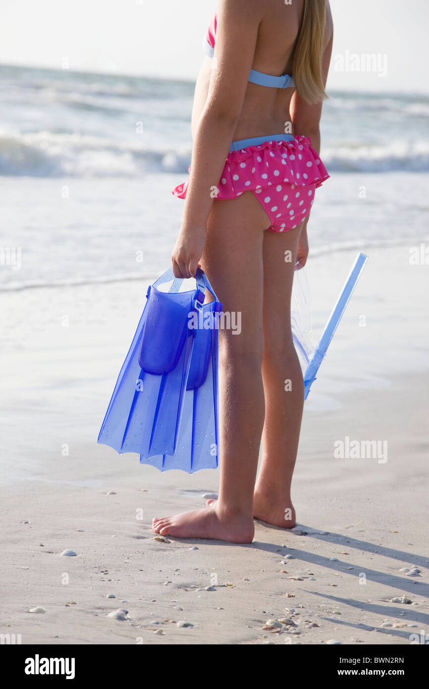 USA, Florida, St. Pete Beach, girl (8-9) holding flippers on beach - Stock Image