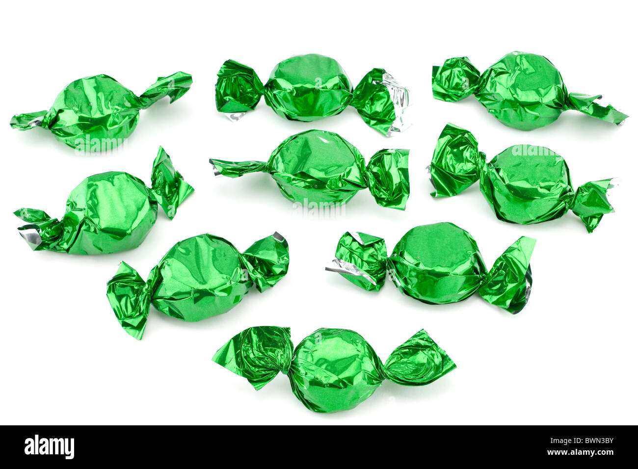 Pile of chocolate sweets wrapped in green silver foil - Stock Image