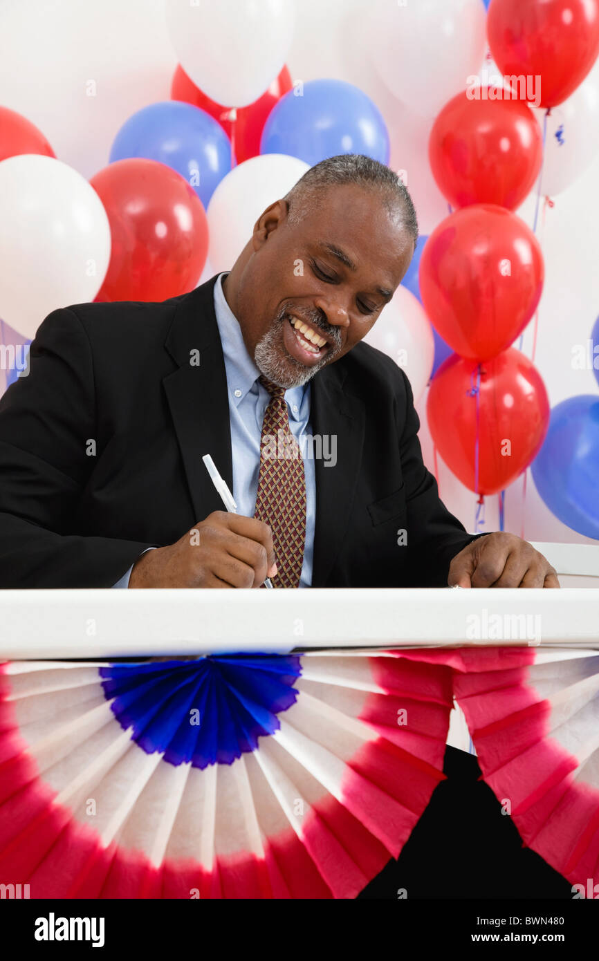 USA, Illinois, Metamora, Smiling man writing at polling place table, balloons in background - Stock Image