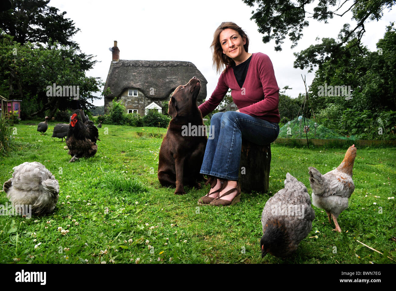 Owner of a thatched cottage with her pet dog and chickens UK - Stock Image