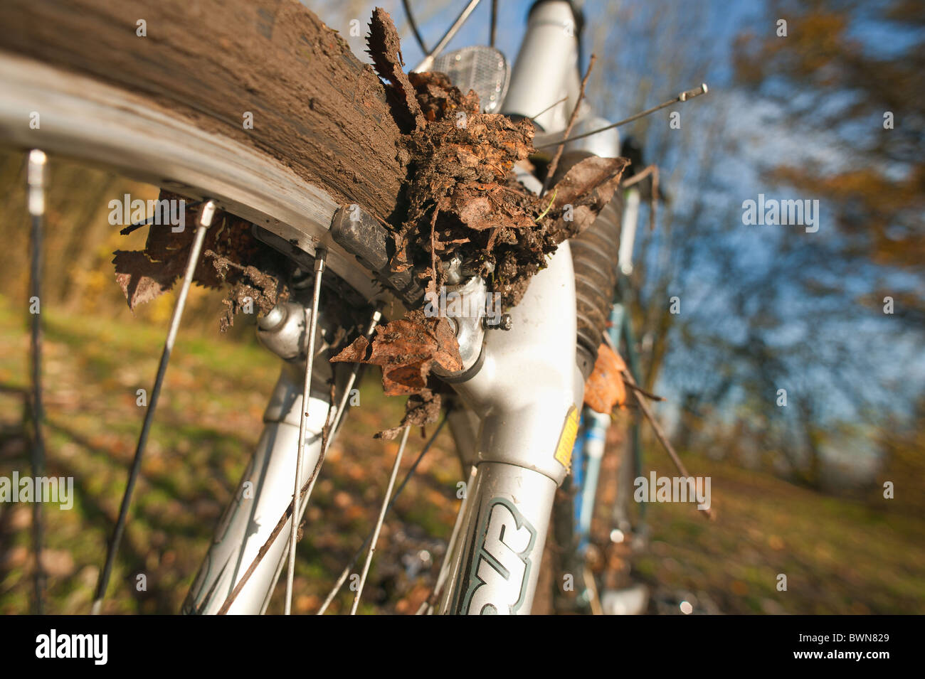 Mountain bike clogged up with mud due to leaves mud and no wheel motion leading to skids uncontrollable maneuver - Stock Image