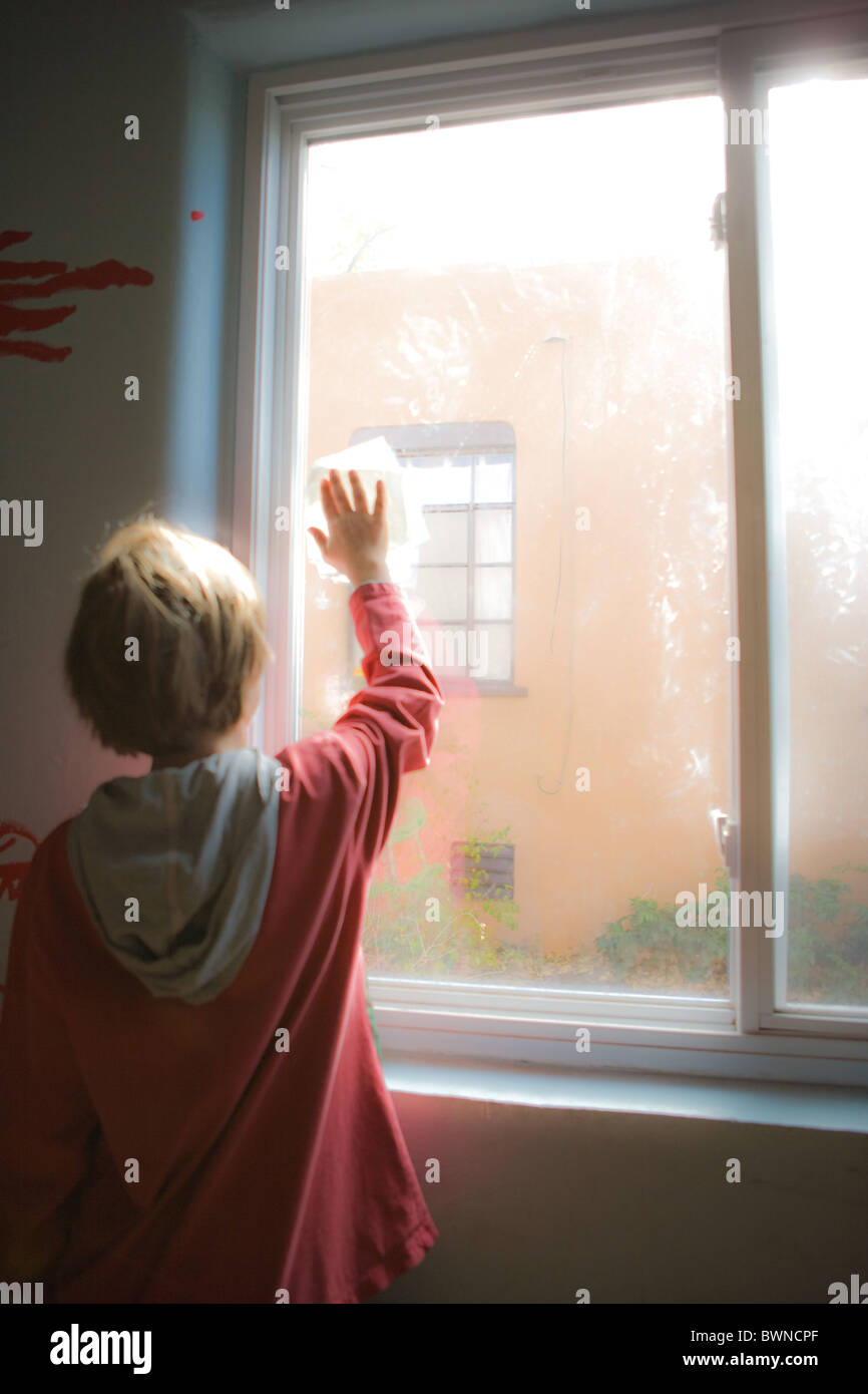 An eight year old boy cleaning a window in his room, light filtering in, vertical. - Stock Image