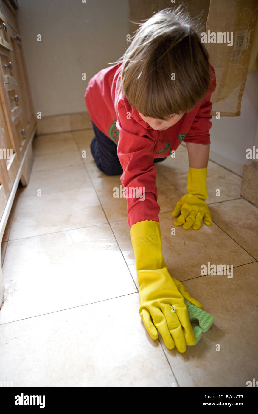 Eight year old boy scrubbing tile on bathroom floor wearing latex gloves, weekly household chore, United States. - Stock Image