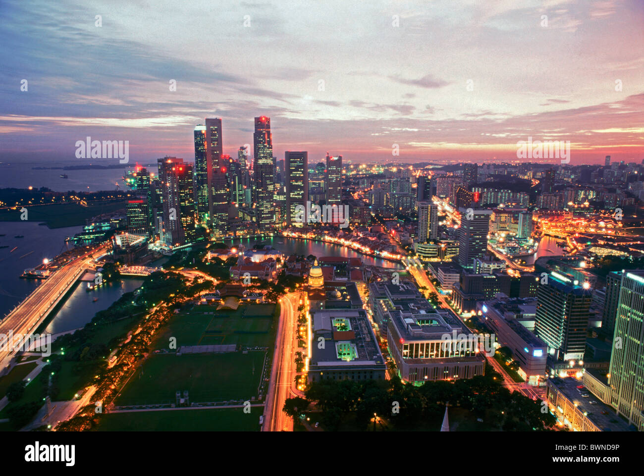 Overview of city lights and central business district of Singapore at sunset - Stock Image
