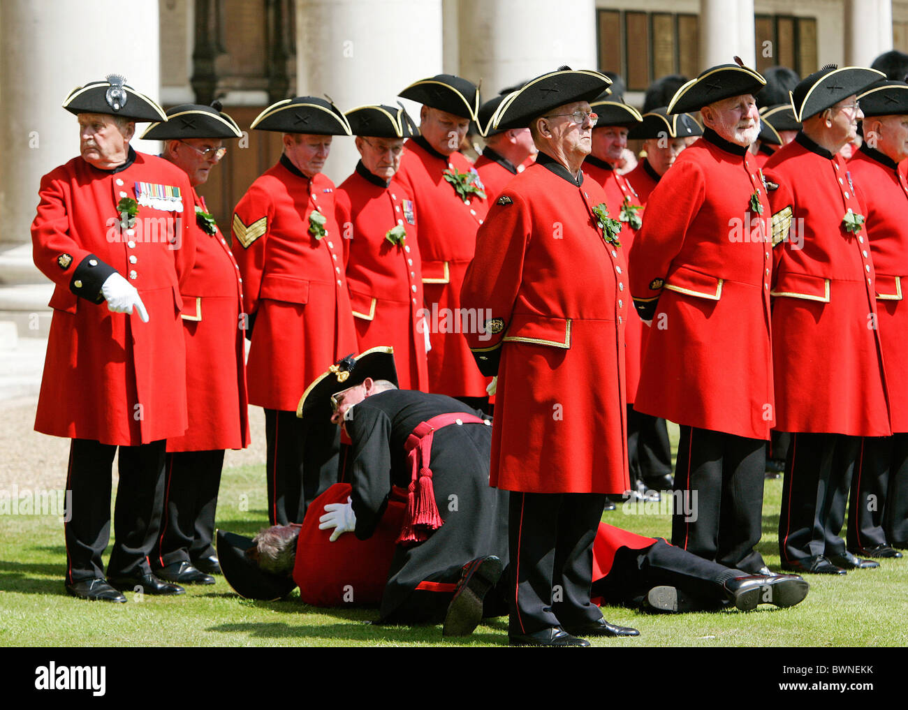 Chelsea Pensioner faints in the heat during the annual Founder's Day Parade at the Royal Hospital in Chelsea - Stock Image