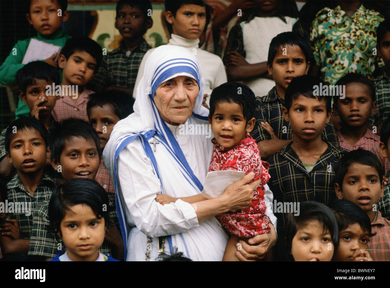 Mother Teresa accompanied by children at her mission in Calcutta, India Stock Photo